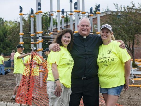Pastor Fr. Mark Brauer with Liz Flynn, President of the Parent Teacher Guild (left) and PTG Treasurer Jamie Shelly.