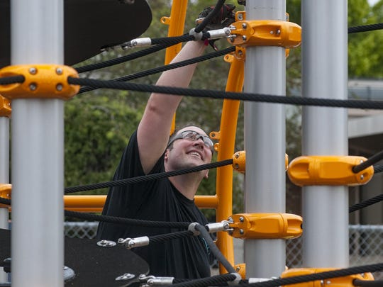Volunteer Jason Cavanaugh double-checks the portion of the playscape he's helping to assemble.