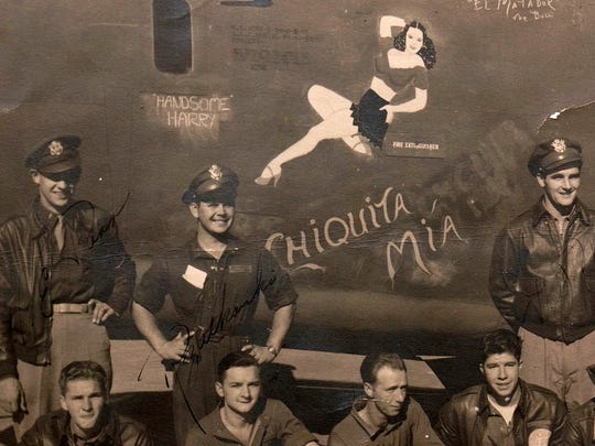 Frank Rogers, hands on hips, with his bomber crew in fron to the Chiquita Mia, his B-24 bomber.