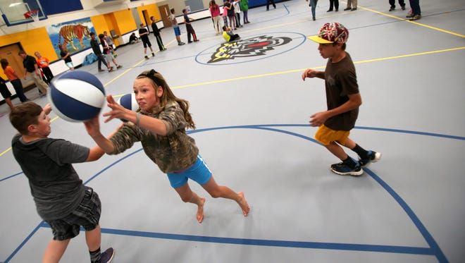 Seventh grader Jaelyn Goodman launches a shot as she and her classmates play a game of knockout during their gym class on the two-week-old floor at St. David Middle School, Thursday, March 30, 2016, in St. David, Ariz. The new crushed rubber base with urethane sealer and paint replaced a floor that was found to be outgassing mercury.