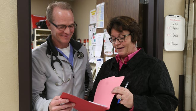 Dr. David Dolins speaks with Jackie Sharp, administrative director for Centerville Community Betterment, on Tuesday in Centerville, Iowa. Sharp often speaks with doctors about patients with mental health problems.