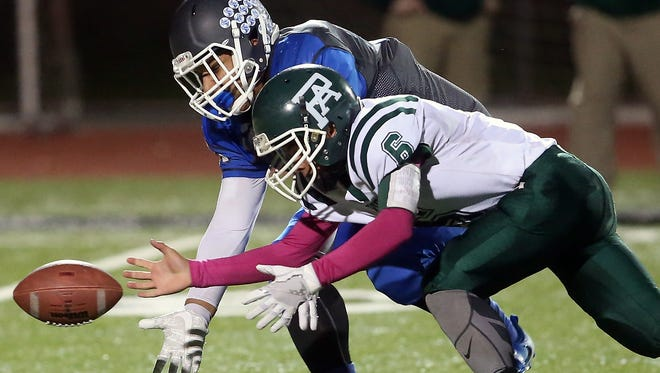 Olympic's Cameron Bailey and Port Angeles quarterback Chris Guttormsen (6) make a grab for a loose ball at Silverdale Stadium on Thursday, October 26, 2017.