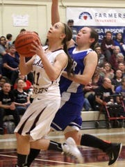 Shania Gililland eyes the basket while being chased by Bryana Muñoz. Gililland led all scorers with 20 points.