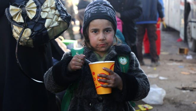 Syrian girl eats after being evacuated to west of Aleppo on Dec. 20, 2016.
