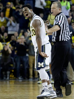 Michigan's Derrick Walton Jr. celebrates after Michigan forced the Minnesota Golden Gophers to turn over the ball during the last minute of play at Crisler Arena.