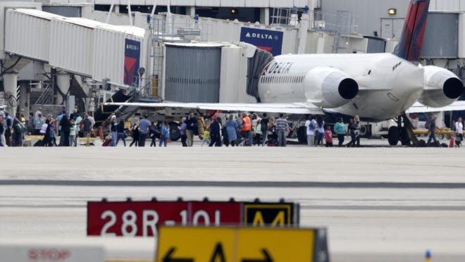 People stand on the tarmac at the Fort Lauderdale-Hollywood International Airport on Friday. A gunman opened fire Friday, killing five people.