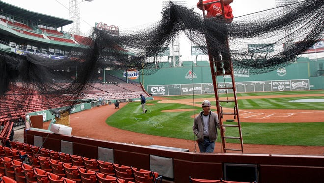 """FILE - In an April 2, 2009 file photo, Local 7 ironworkers Kevin McConologue, on ladder, and Scott White put protective netting in place over the seating behind home plate at Fenway Park in Boston. Boston Red Sox president Sam Kennedy announced Saturday, Jan. 20, 2018 that the team is planning what he calls a """"dramatic"""" expansion of safety netting at Fenway Park.  He says the netting will be extended past the dugouts on both the left field and right field lines. (AP Photo/Elise Amendola, File) ORG XMIT: NYSP101"""