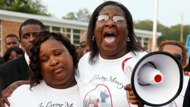 Frances Sanders, mother of Jonathan Sanders, hugs his sister Nicole Holloway, as she calls for justice during a remembrance and rally for Sanders in Stonewall, Miss., Sunday, July 19, 2015. Sanders died after a physical encounter with a white police officer on July 8, and had been riding in a two-wheeled buggy pulled by a horse.