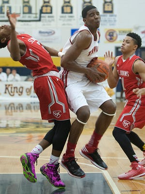 St. John's (Wash. D.C.) Cadets guard  Tre Wood, left, falls back after connecting with a driving Taylor County Cardinals guard Quentin Goodin. At right is St. John's (Wash. D.C.) Cadets guard  Anthony Cowan Jr.