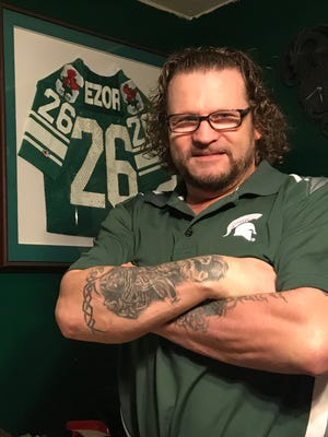 Blake Ezor, 51, poses in his Las Vegas home office where his Michigan State Rose Bowl and Gator Bowl jerseys hang from the wall.