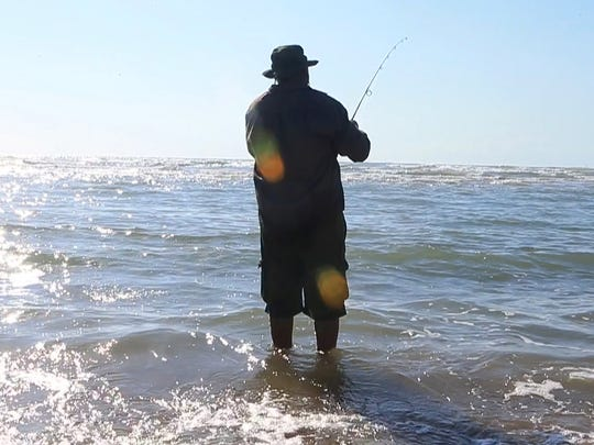 A man fishes in the Gulf of Mexico near the mouth of the Rio Grande.
