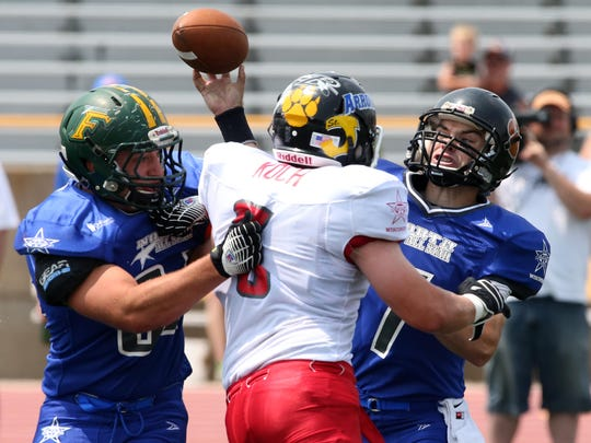 North's Ethan Young throws a pass as Mason Sturm fights off Zach Koch during the All-Star football game in July 2014 at J.J. Keller Field of Titan Stadium.