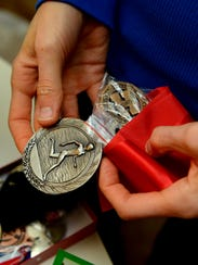 Allison Rademacher holds old cross country medals from