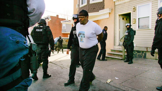 Gene Watson is arrested by SWAT team members after a December 2004 search of his home at East 23rd and  Lamotte streets uncovered about 12.5 grams of crack cocaine, 30 $10 bags of heroin, about 1.75 grams of marijuana, plastic bags often used in packing drugs, a scale and $1,116 in cash.