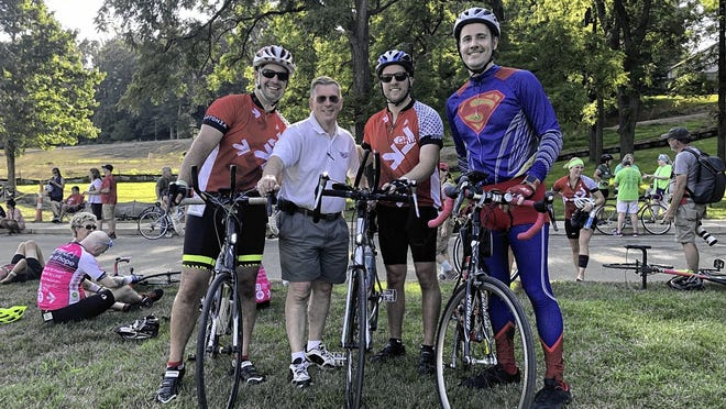 Patrick Rogers (right), wearing his signature Superman costume, poses with (from left) his brother, Phillip Rogers, his father-in-law, Tim Heron, and his brother, Alex Rogers, before riding in Pelotonia in 2019. Rogers will continue his Pelotonia fundraising this year by wearing a collared golf shirt with a large Superman emblem as he tries to finish as many holes of golf as he can at St. Albans Golf Club in Alexandria with childhood friends Brad Highland and Matt Highland.