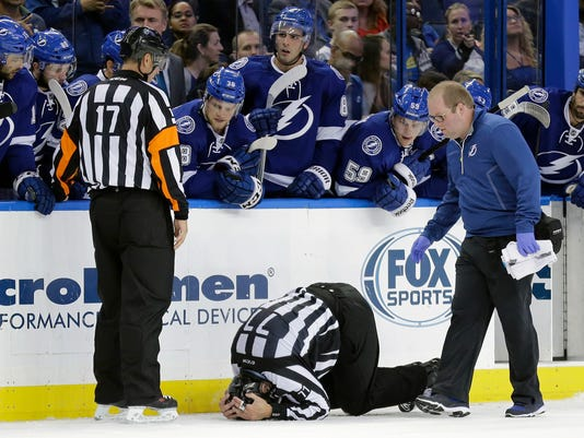 NHL linesman Tim Nowak (77) covers his head after he was injured during the second period of an NHL preseason hockey game between the Tampa Bay Lightning and the Nashville Predators on Tuesday, Sept. 23, 2014, in Tampa, Fla. Looking on is referee Frederick L'Ecuyer (17). (AP Photo/Chris O'Meara)