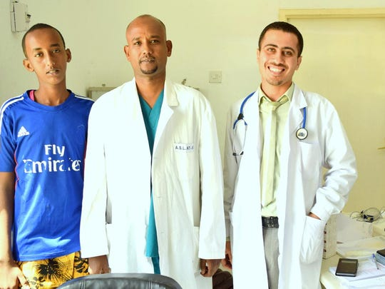 Dr. Adan Muse, center, is the director of Kaamil Hospital in Somalia. He came back from Italy to work in Somali Health Sector. He is shown with another doctor and a young Somali patient who had brain surgery after a bad accident.