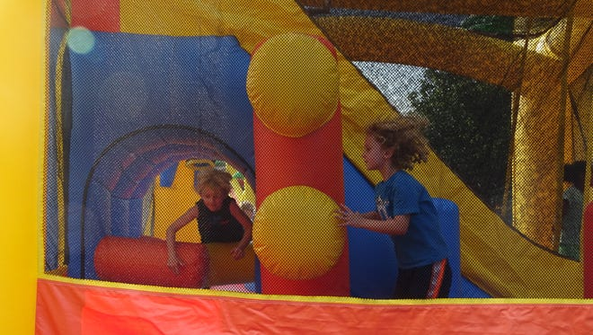 Kids play in the inflatable bounce houses at National Night Out Tuesday.