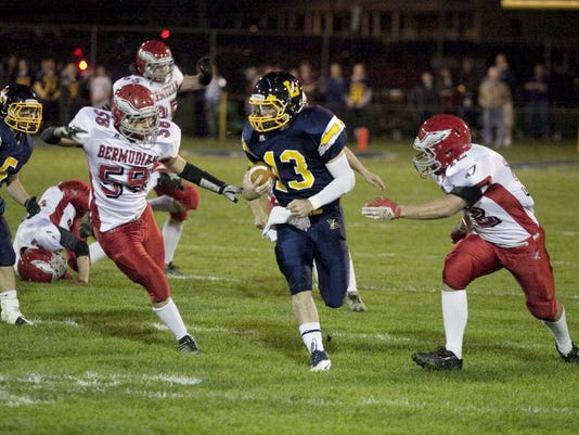 Littlestown's Dustin Crouse attempts to carry the ball while Bermudian Springs' Austin Hartzell, left, and Sean McManama, right, close in for a tackle during Friday's game at Littlestown.