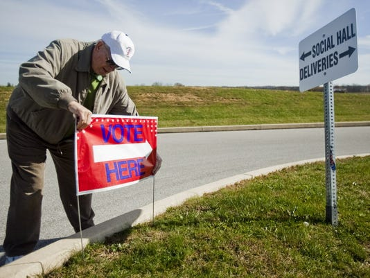 Barry Bower, of Brushtown, sets up signs on at the SAVES fire hall in preparation for elections in 2013. (File - The Evening Sun )