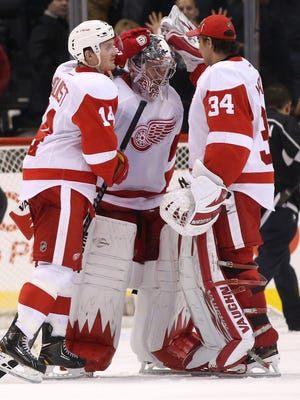Goalie Jimmy Howard, center, of the Detroit Red Wings is congratulated by Gustav Nyquist, left, and Petr Mrazek after a game against the Los Angeles Kings on Jan. 11, 2014.