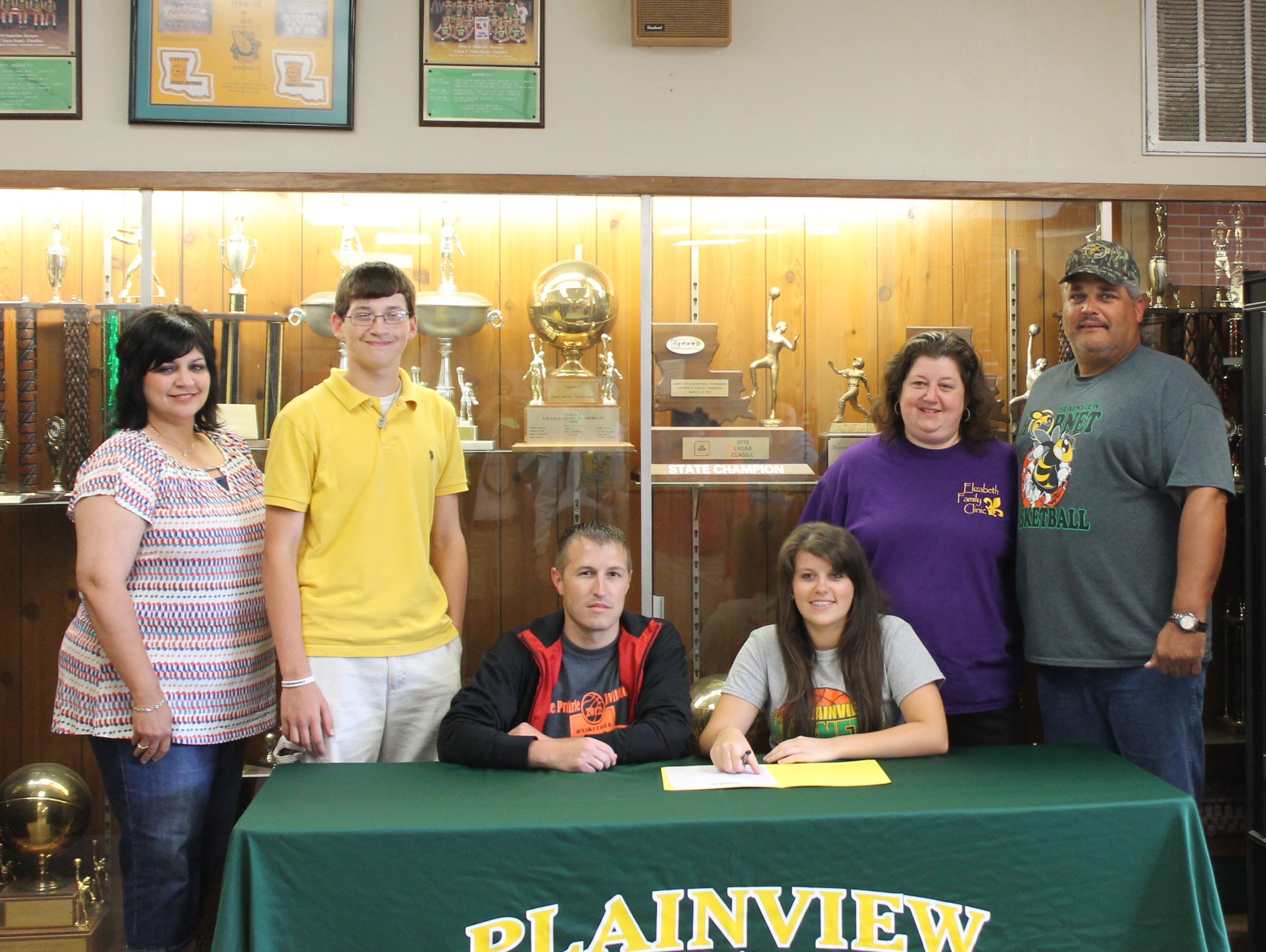 Plainview senior Kelli Crager (seated, right) signs with LSUA and is joined by (from left): Plainview principal Sonia Rasmussen; her brother, Michael; Plainview coach Justin Miller and her parents Michelle and Mike.