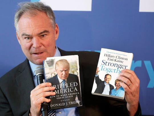 Sen. Tim Kaine, D-Va. holds up books to show the difference