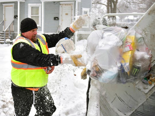 Garbage collector Paul Fairbanks empties trash in Syracuse, N.Y., Friday, Jan. 5, 2018. Frigid temperatures, some that felt as cold as minus 30 degrees, moved across the East Coast on Friday as the region dug out from a massive winter storm that brought more than a foot of snow, hurricane-force winds and coastal flooding a day earlier. (Scott Schild /The Syracuse Newspapers via AP)