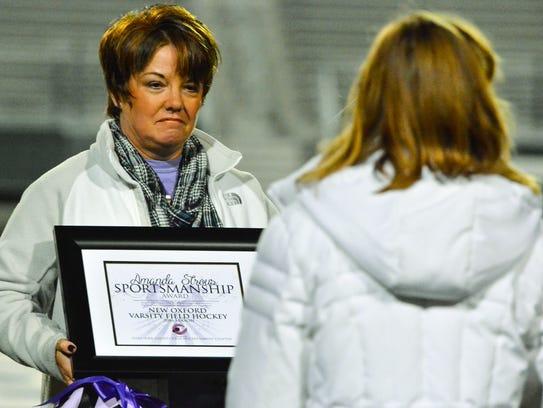 Crystal Strous, left, presents the Amanda Strous Sportsmanship