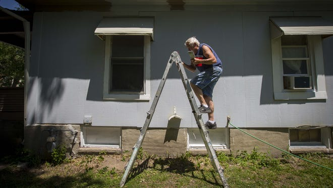 Gene Devore paints the soffit of a home at 3511 6th Ave. in Des Moines Friday, June 30, 2017. Devore has worked for over 20 years for Gary Oeth.