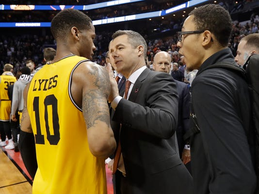 Virginia coach Tony Bennett, center, congratulates UMBC's Jairus Lyles, left, after a first-round game in the NCAA men's college basketball tournament in Charlotte, N.C., Friday, March 16, 2018. (AP Photo/Gerry Broome)
