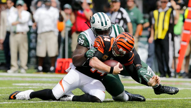 Cincinnati Bengals quarterback Andy Dalton (14) is sacked by New York Jets defensive tackle Steve McLendon (99) in the second quarter of the NFL Week One game between the New York Jets and the Cincinnati Bengals at MetLife Stadium in East Rutherford, N.J., on Sunday, Sept. 11, 2016. At halftime, the Bengals trailed 16-13.