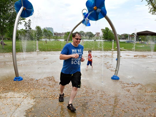 John Storrs and his son Logan, 4, race around Thursday at the Lake George splash pad.