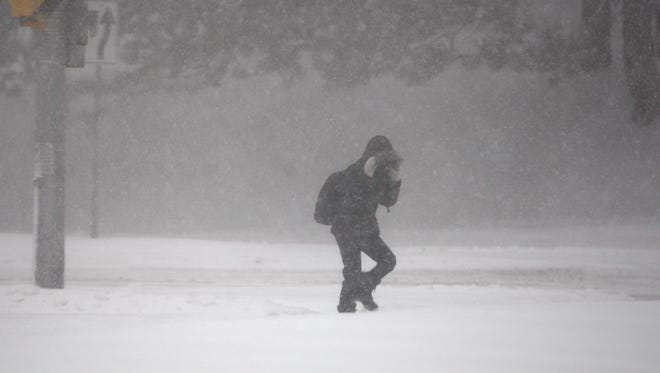 A pedestrian braces against a gust of wind on Elmwood Avenue near Kendrick Road in Rochester.