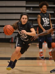 Rhiana Dougan, a shooting guard for the Ventura College women's basketball team, goes through practice drills as teammate Kyleesha Green watches and Jacari Jackson works with her.