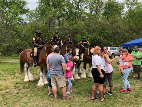 Local residents pet Clydesdales with mounted officers Saturday at Glasgow Park.