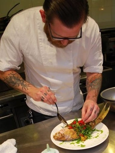 Chef Herget garnishes whole fried snapper at Little