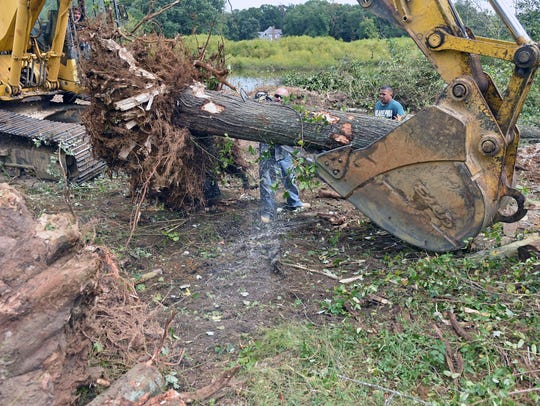 Workers from Fred M. Schiavone Construction use a backhoe