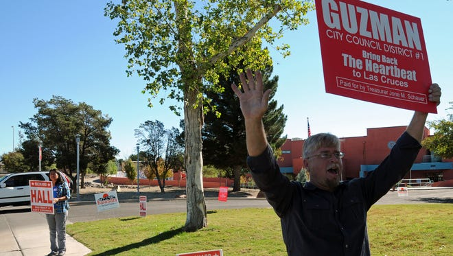Richard Hall, a candidate for the District 4 seat on the Las Cruces City Council, holds a sign for a candidate running for a different council seat — District 1's Eli Guzman — in front of the Branigan Library on Tuesday. Hall's wife Lupe stands nearby holding a sign promoting her husband's candidacy.