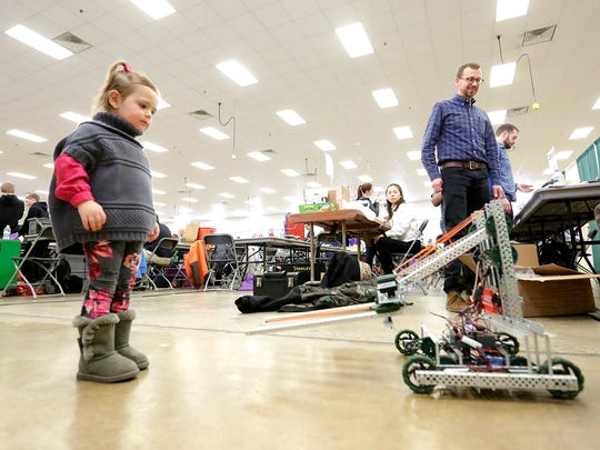 Brynn Bogenhagen of Lomira admires a robot Saturday morning at the fourth-annual Ishamon Harris Memorial VEX Robotics Competition Tournament held at the Fond du Lac Fairgrounds.