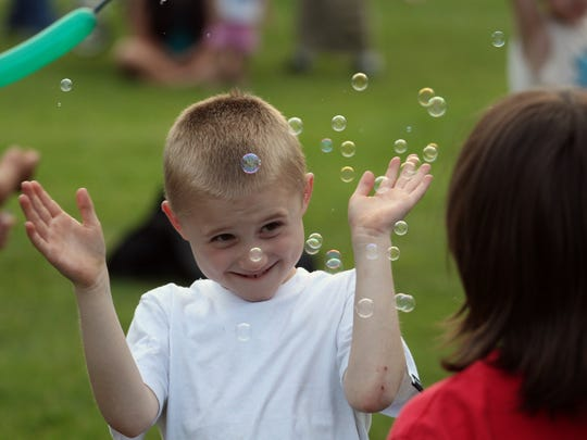 Phillip Hebbe, 7, of Wausau, bats at bubbles blown by Casey Romansik, 8, of Wausau, right, during Wausau's 2013 Summer Kickoff Celebration at Oak Island Park.