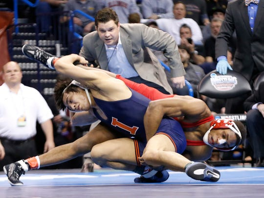 Cornell's Nahshon Garrett, right, wrestles Illinois' Jesse Delgado, left, in the 125-pound match in the finals of the NCAA Division I wrestling championships in Oklahoma City, on March 22, 2014. Delgado won the match and the championship.
