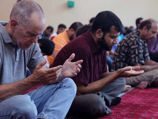 David Osgood, far left, Mohsinur Rahman, center, participate in an afternoon prayer Friday June 3, 2016 at the Islamic Center of WIllimason County.