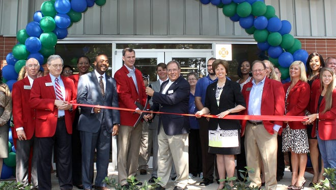 Goodwill president and CEO Fred Shelfer, center, prepares to cut the ribbon Thursday to officially open the new Prosperity Center on Mabry Street.