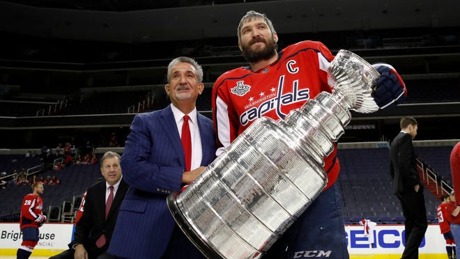Washington Capitals NHL hockey team owner Ted Leonsis, left, and Washington Capitals left wing Alex Ovechkin, from Russia, pose for picture with the Stanley Cup on the ice at Capital One Arena, Tuesday, June 12, 2018, in Washington. (AP Photo/Alex Brandon)
