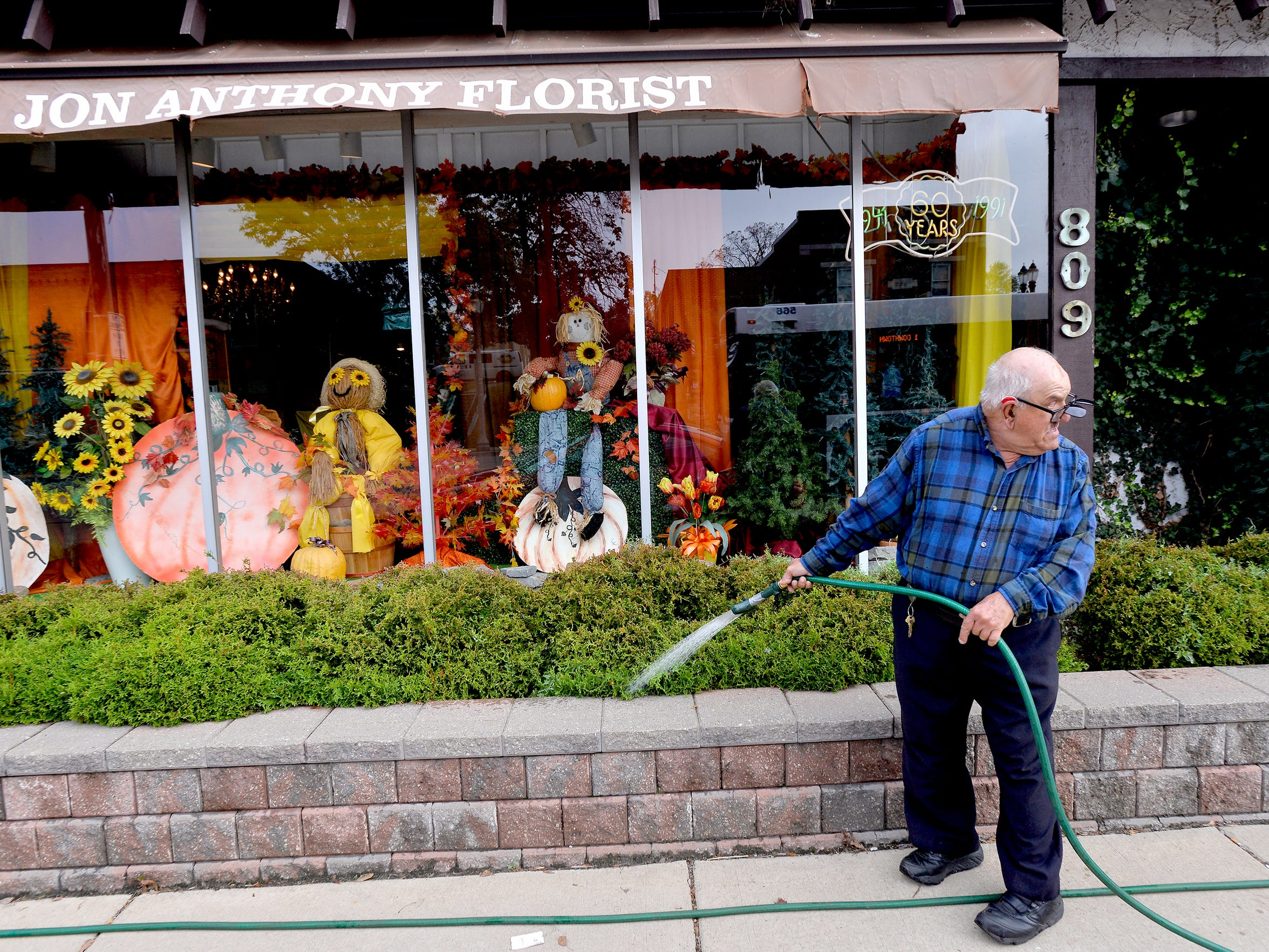 Tony waters plants as he does odd jobs at longtime employer Jon Anthony Florist in Lansing before making his daily walk to hang out at  Lansing's Fire Station One.