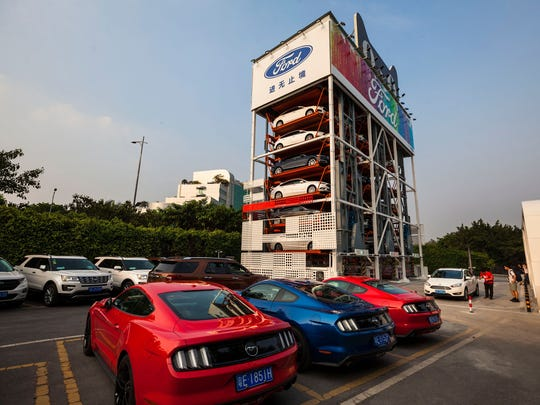 "Ford Mustangs are for sale in a vending  machine in Guangzhou, Guandong Province, China,  April 2018. The Alibaba Group and Ford have unveiled a ""No staff"" car vending machine standing five-stories tall and contains 42 cars."