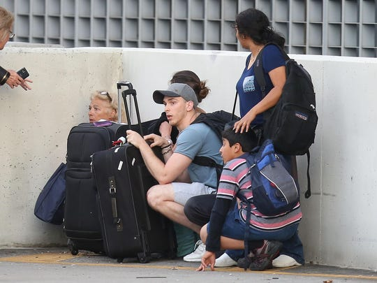 Passengers take cover as first responders secure the area outside the Fort Lauderdale-Hollywood International airport after a shooting took place near the baggage claim on Friday, Jan. 6,  in Fort Lauderdale.