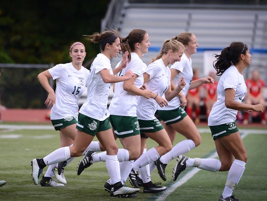 Mia Suchora (no. 12, center) of Ramapo is congratulated