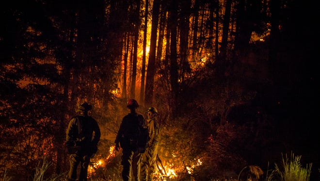 Firefighters keep a watchful eye on the Carr Fire as it burns into the evening along Highway 299, just east of the Trinity County line Monday July 30, 2018. Firefighters made progress with the fire, which was over 20 percent contained by the evening.(KELLY JORDAN / USA TODAY NETWORK)